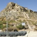 La máquina retroexcavadora trabaja en la ladera cubierta por las redes metálicas que sujetan las rocas. :: SONIA M. LARIO / AGM